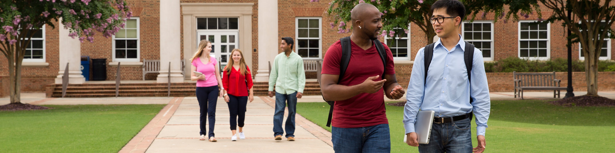 Five students walking in discussion on Cary Academy campus