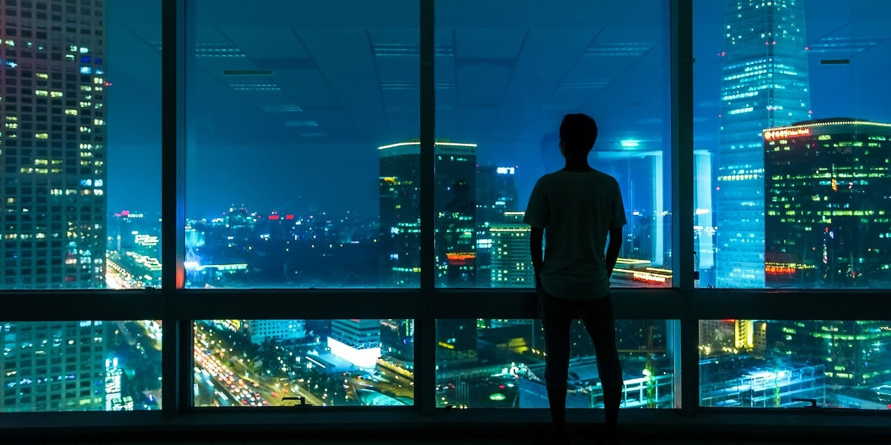 Man starring at city through window at night