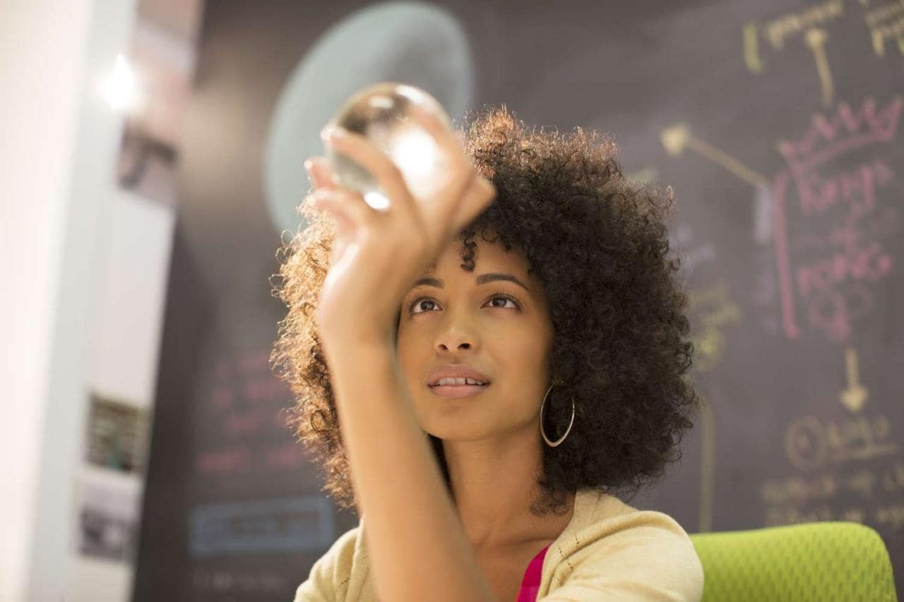 Businesswoman examining crystal ball in office