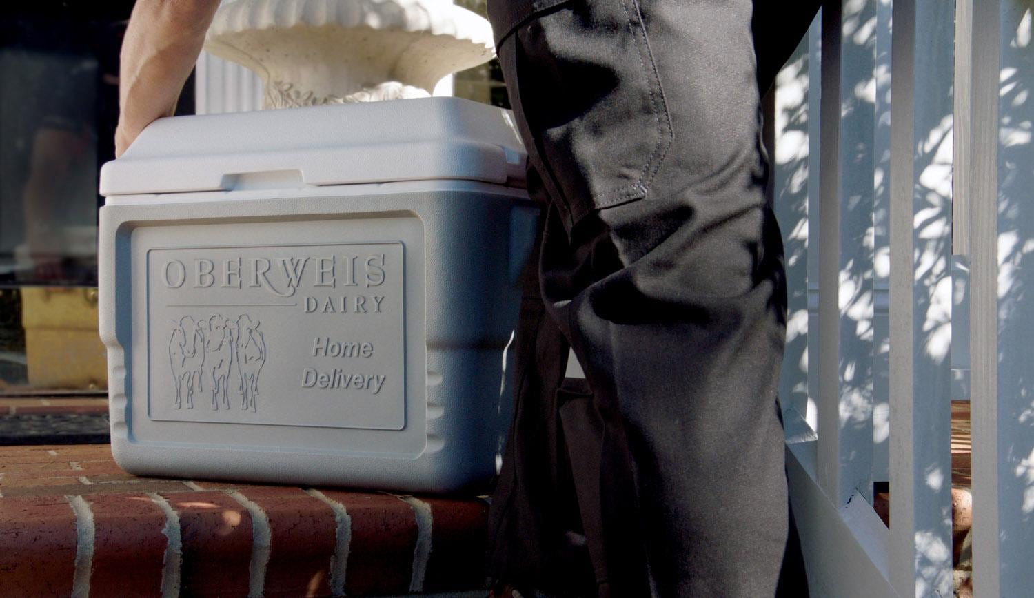 Oberweis delivery man placing cooler of milk on front porch
