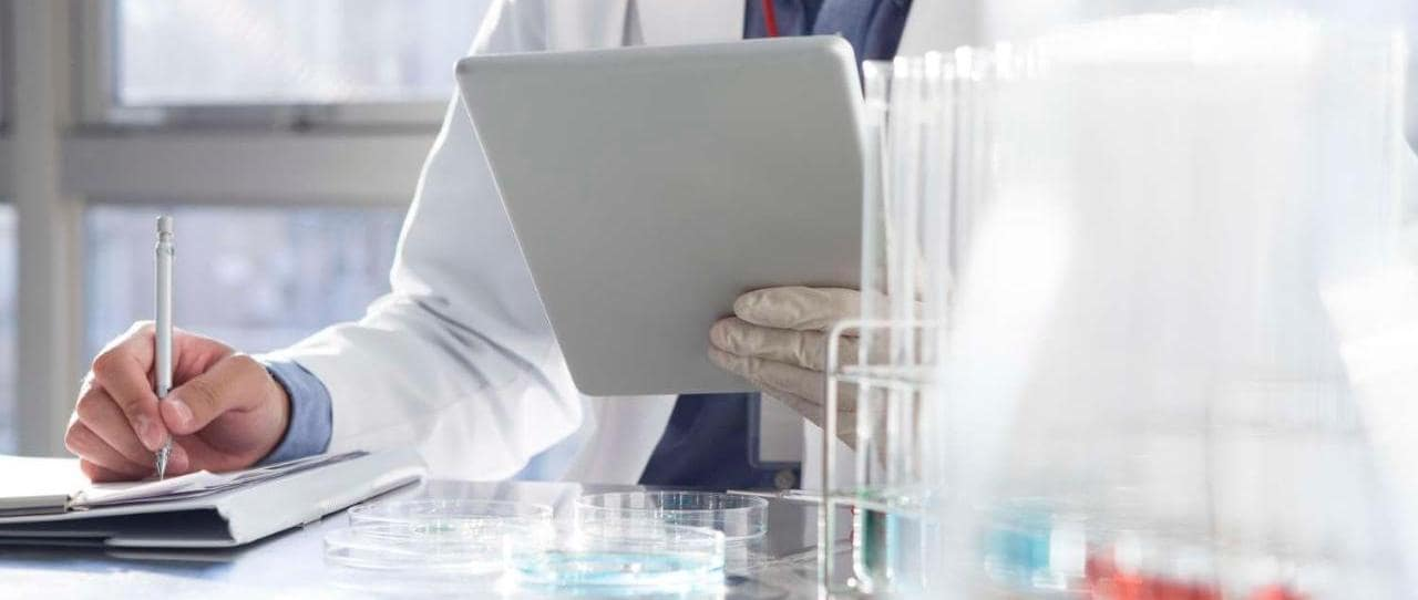 Scientist reading an electronic tablet while filling out a document