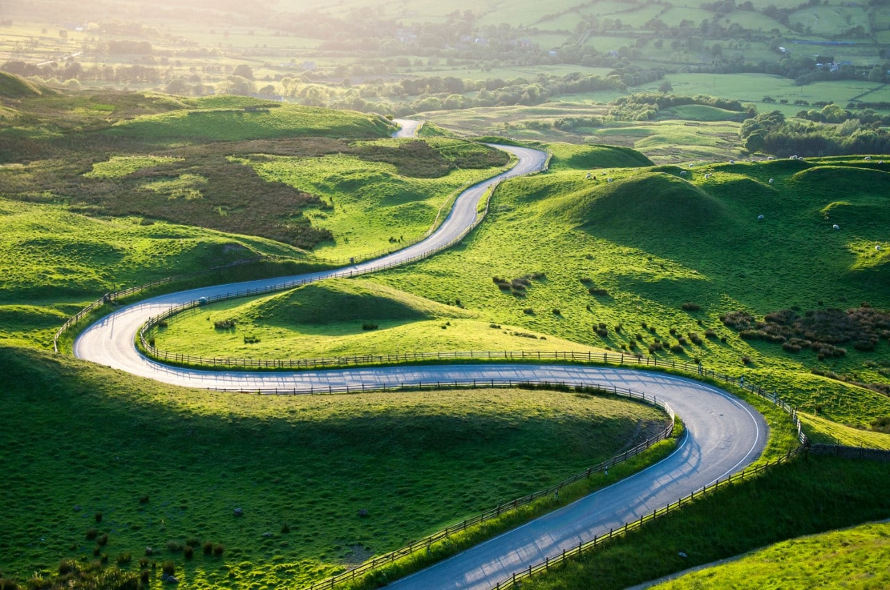 Road bends and weaves in green landscape