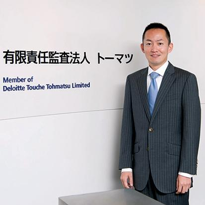 Asian business man standing inside in front of wall at Japan Tohmatsu Deloitte Touche building