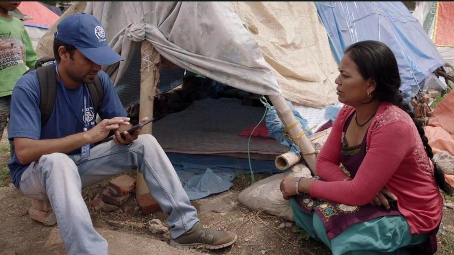IOM staff  member reviewing analyses via cell and gathering data from Nepalese woman