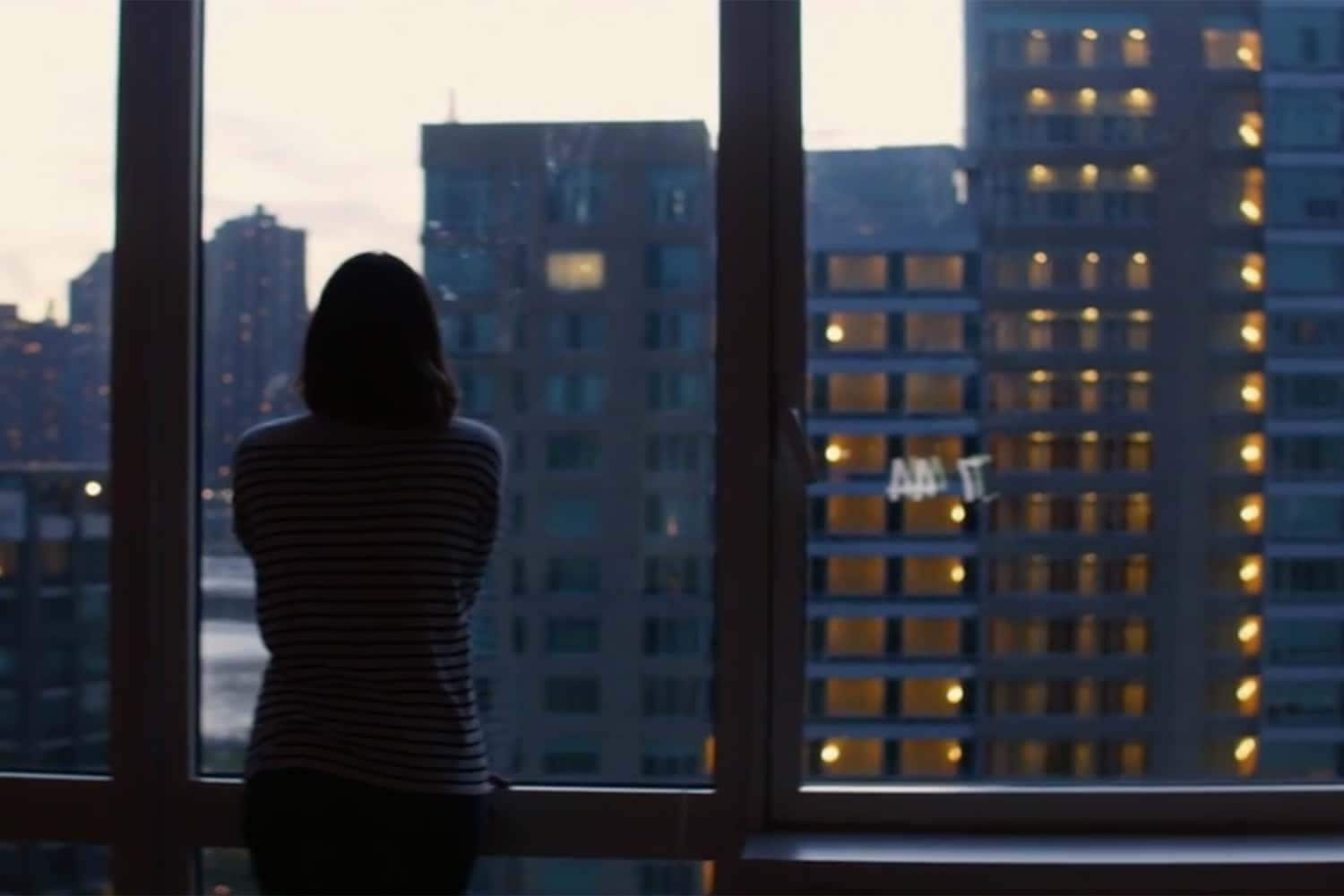 Businesswoman looking out city window