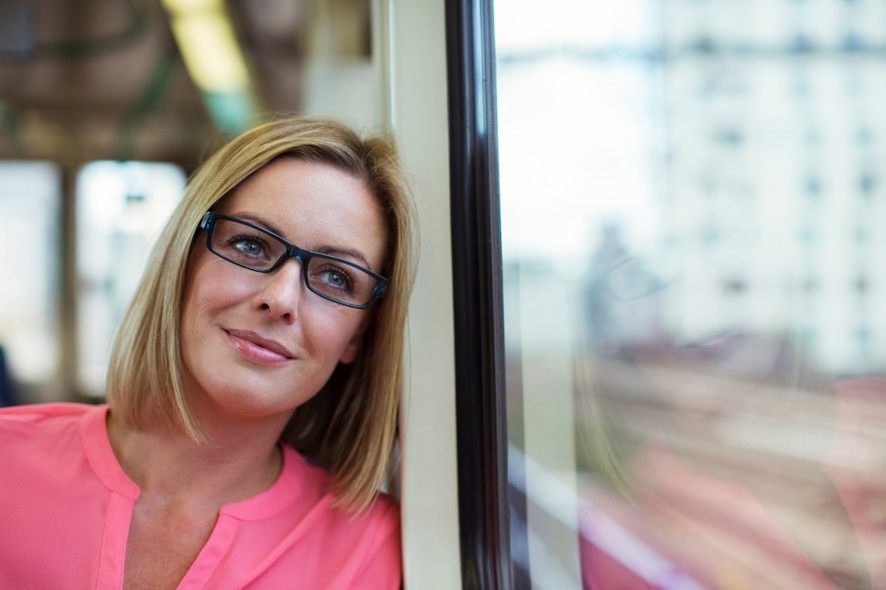 Smiling woman looking out train window