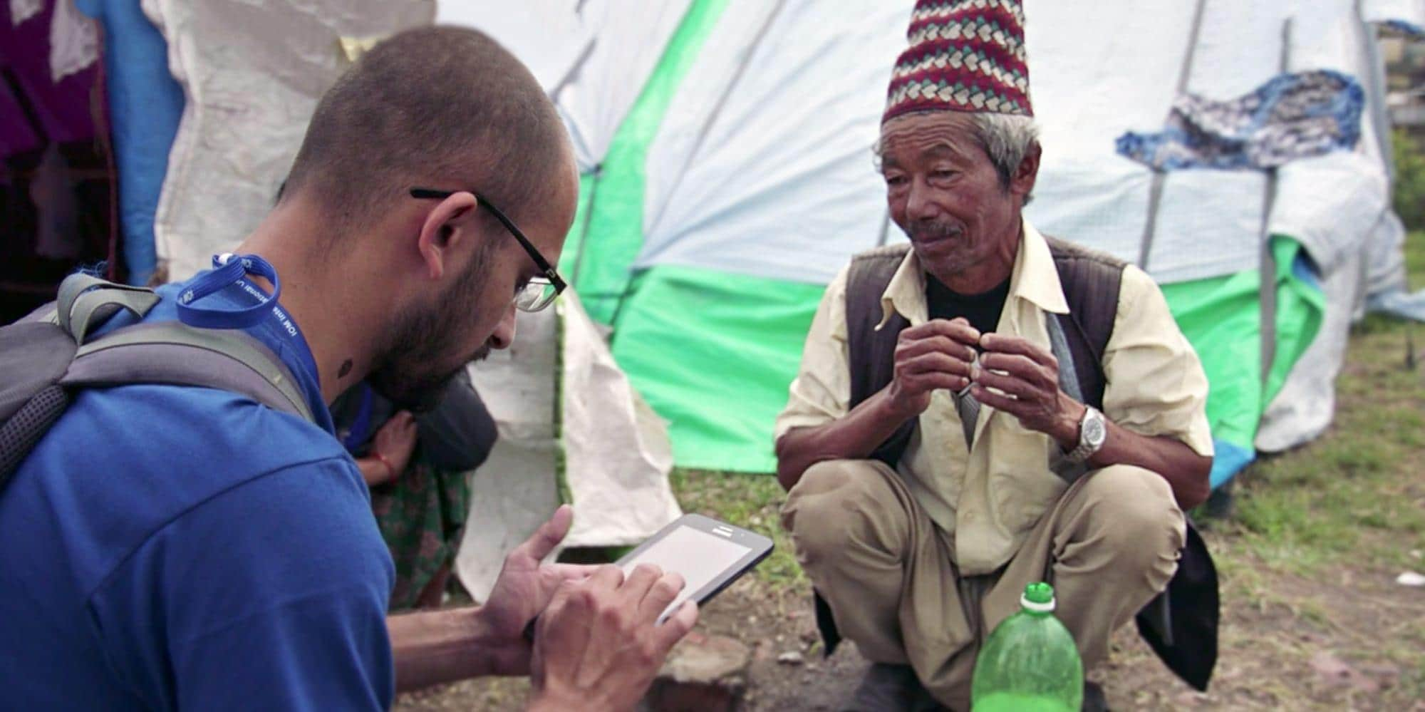 IOM Worker Using Tablet and Talking With Man After Earthquake