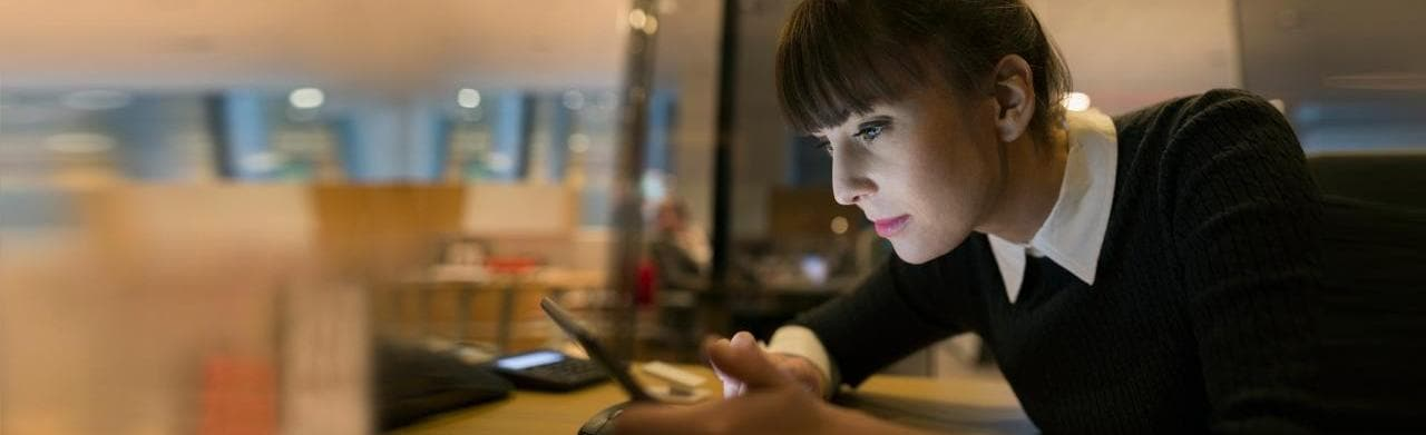 Woman staring intently at tablet device