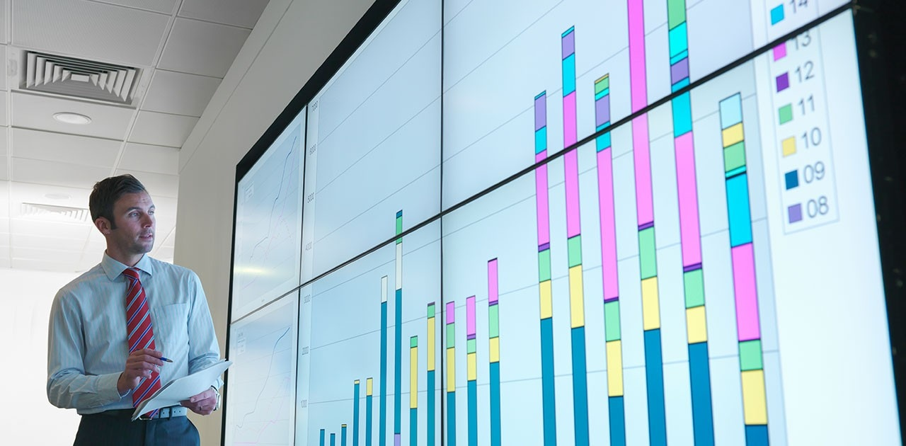 Businessman with graphs on screen
