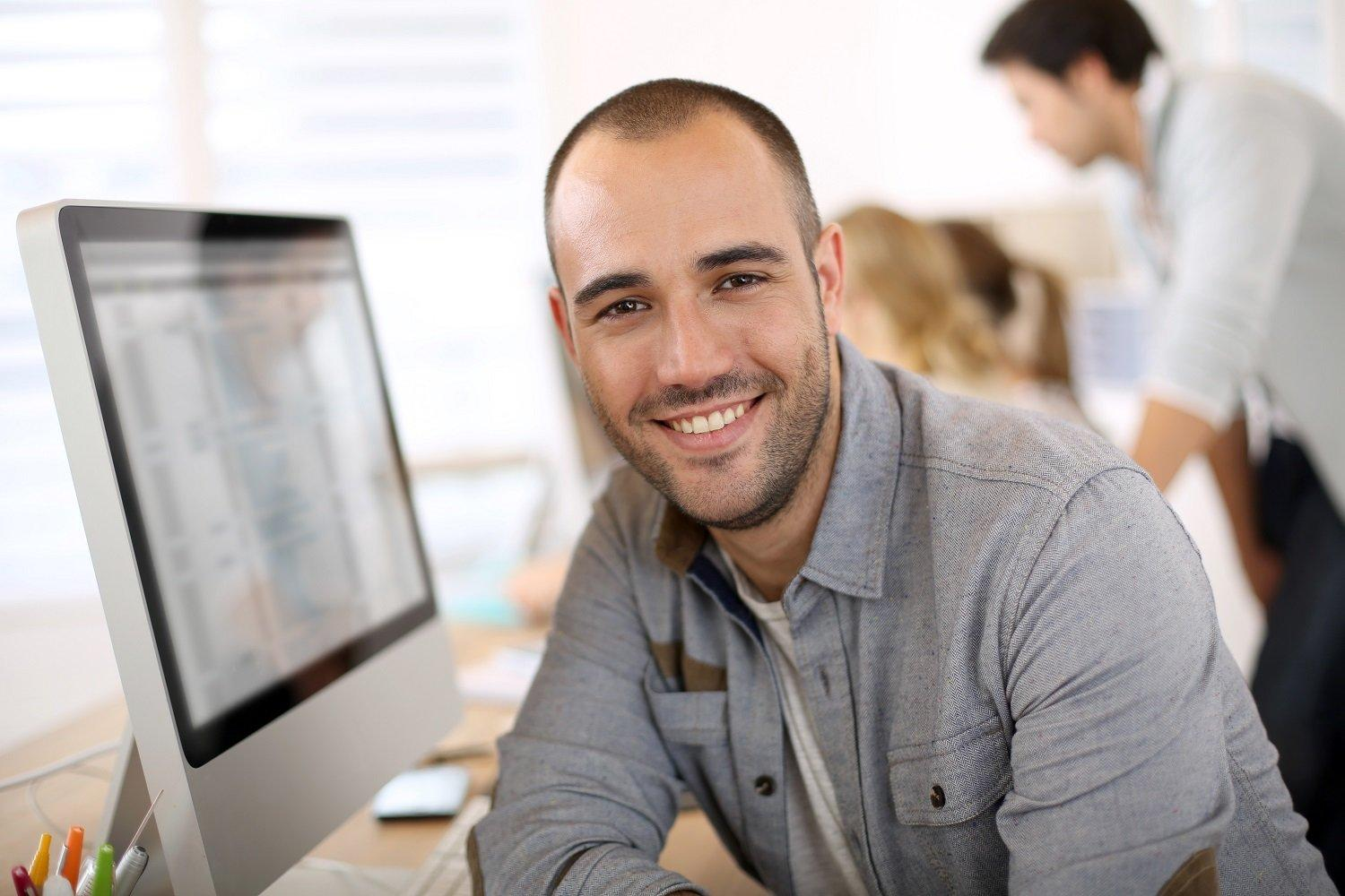 man behind computer smiling