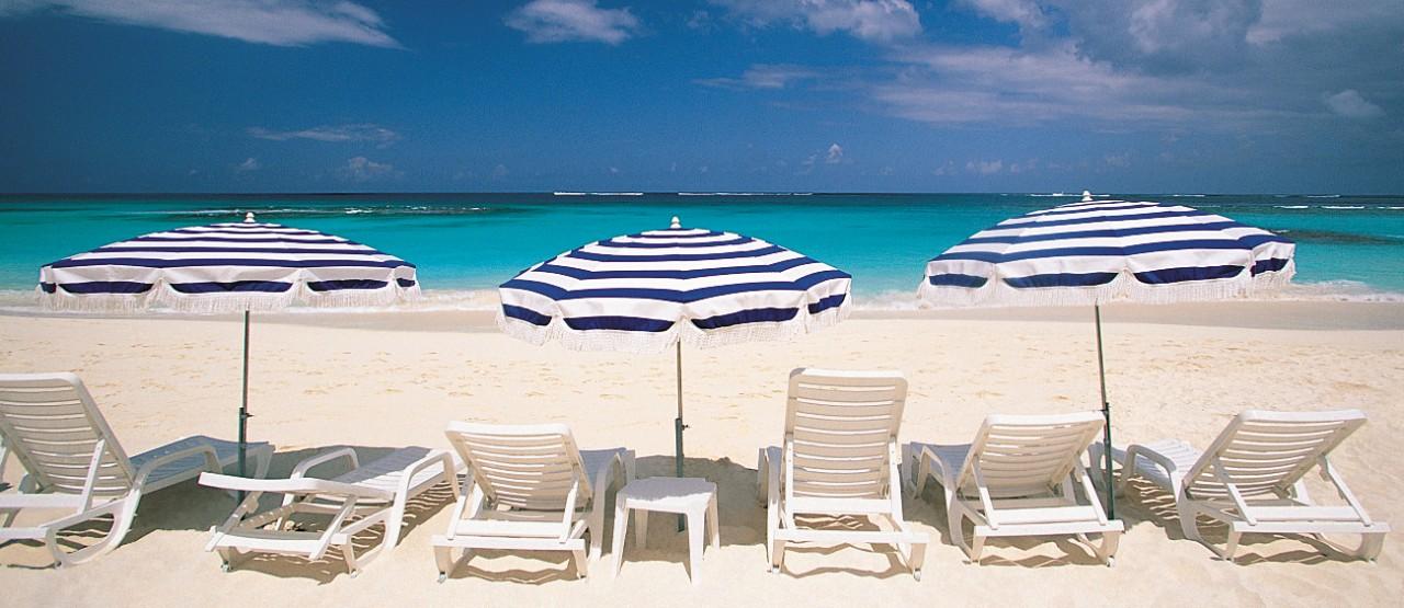 Open beach chairs and beach umbrellas facing ocean