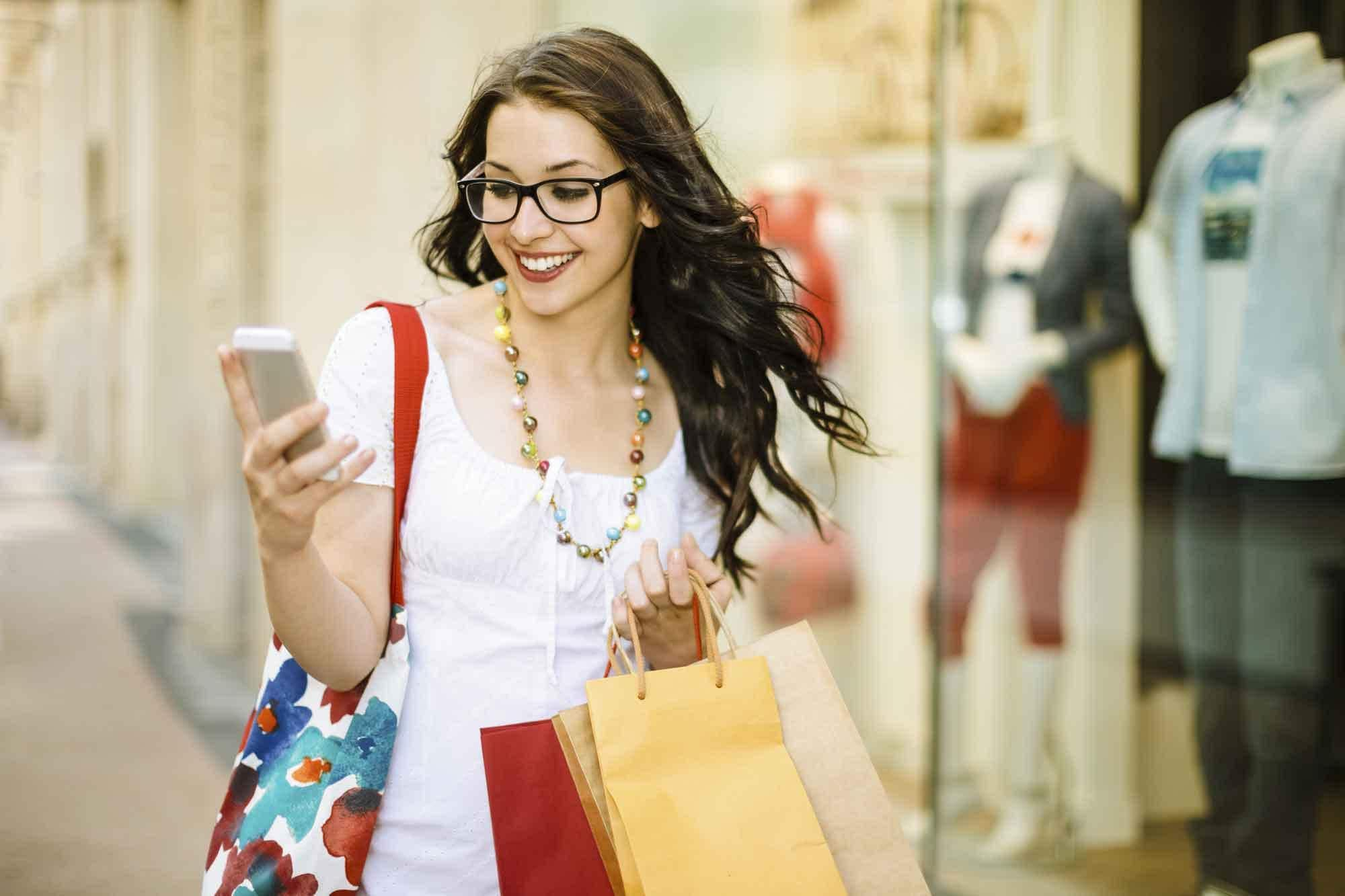 Woman carry shopping bags using phone