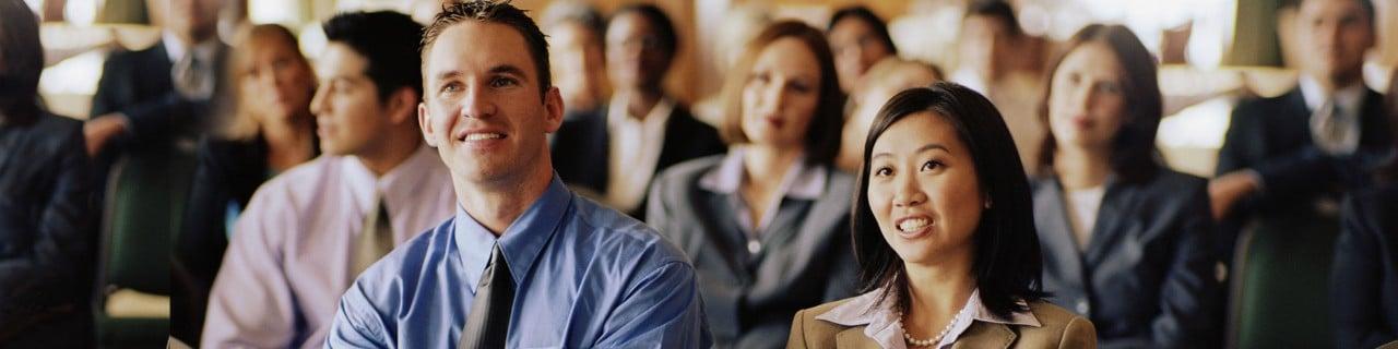Group of businessmen and businesswomen smiling, listening to speaker