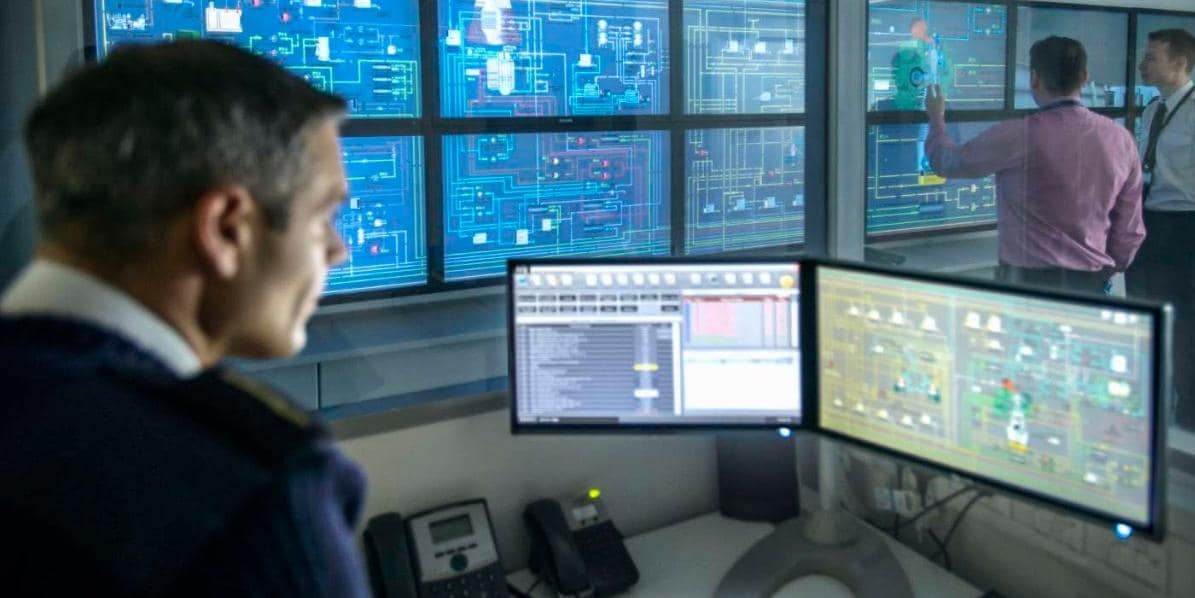 Security control center workers looking at data on computer screens