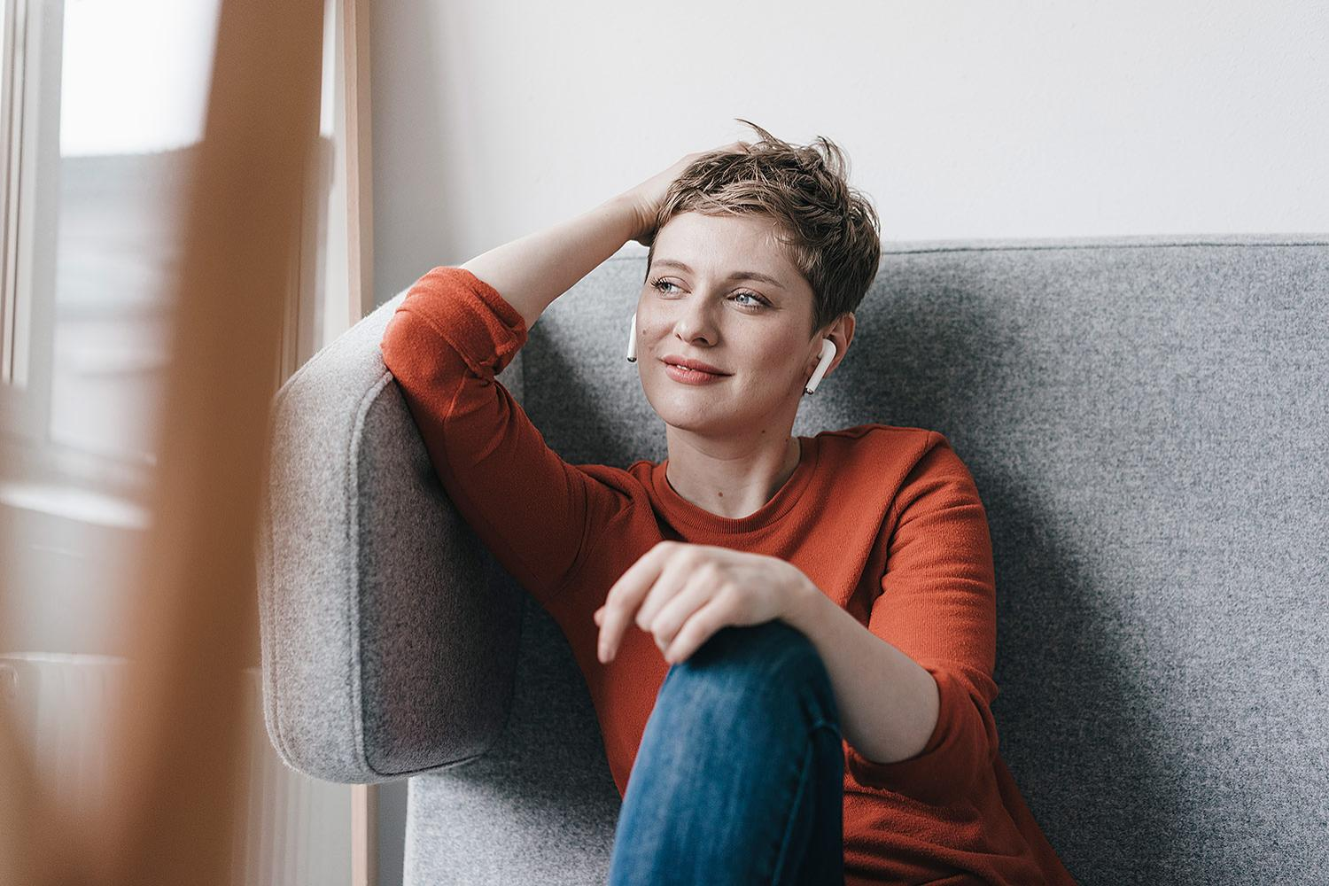 Woman with Airpods sitting in sofa