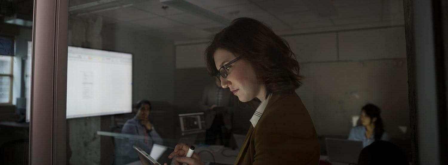 Businesswoman using digital tablet dark conference room meeting
