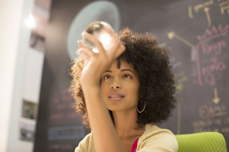 Woman looking at glass ball with chalkboard in background