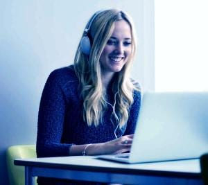 Young woman wearing headphones using desktop with blue layer