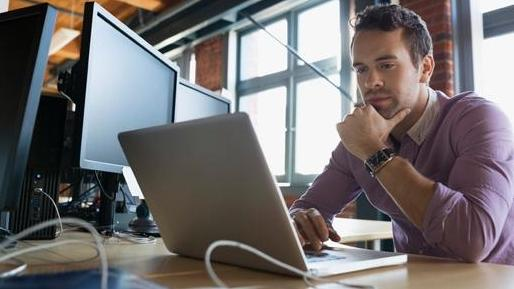 Pensive man working on a laptop surrounded by monitors