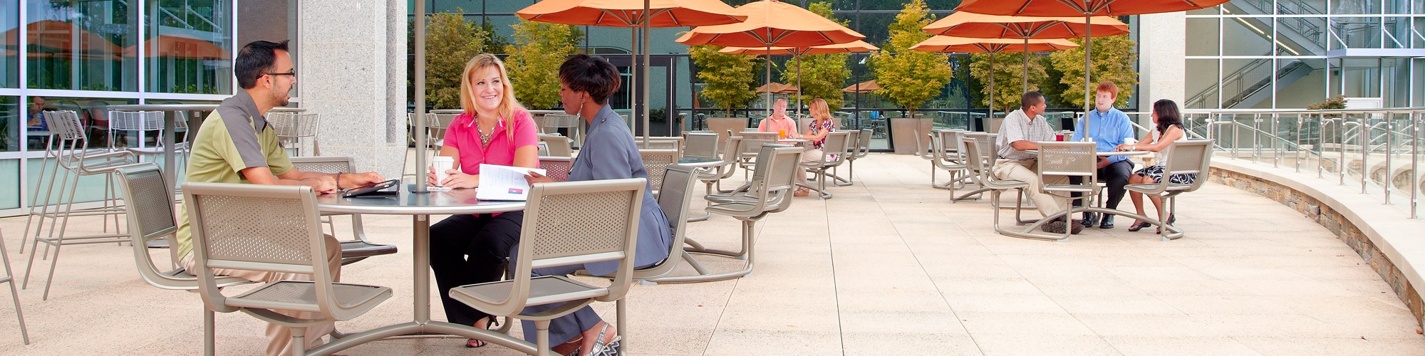 Employees sitting at tables of outdoor patio area at SAS headquarters in Cary NC