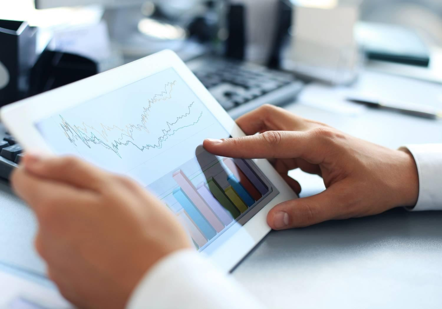 An office worker -- close-up image of an office worker using a touchpad to analyze statistical data