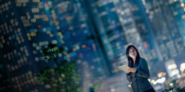 Woman with Tablet in the City at Night