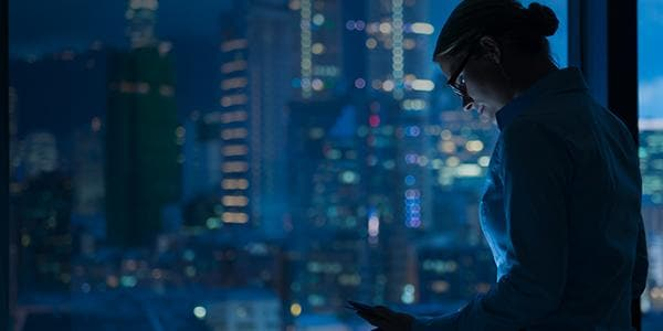 woman looking at device with dark city background