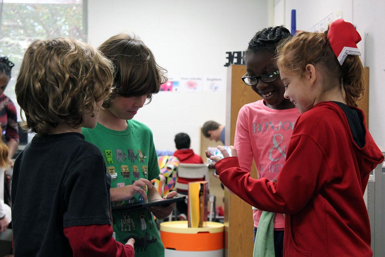 Group of young students using CodeSnaps app and holding robotic sphere