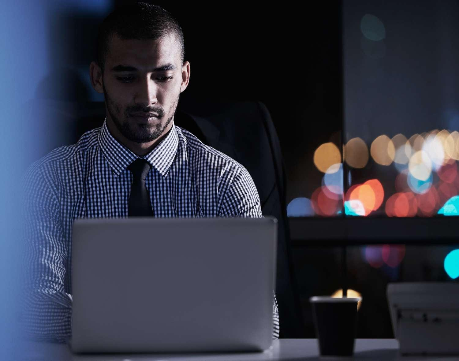 Man with tie on a laptop at night