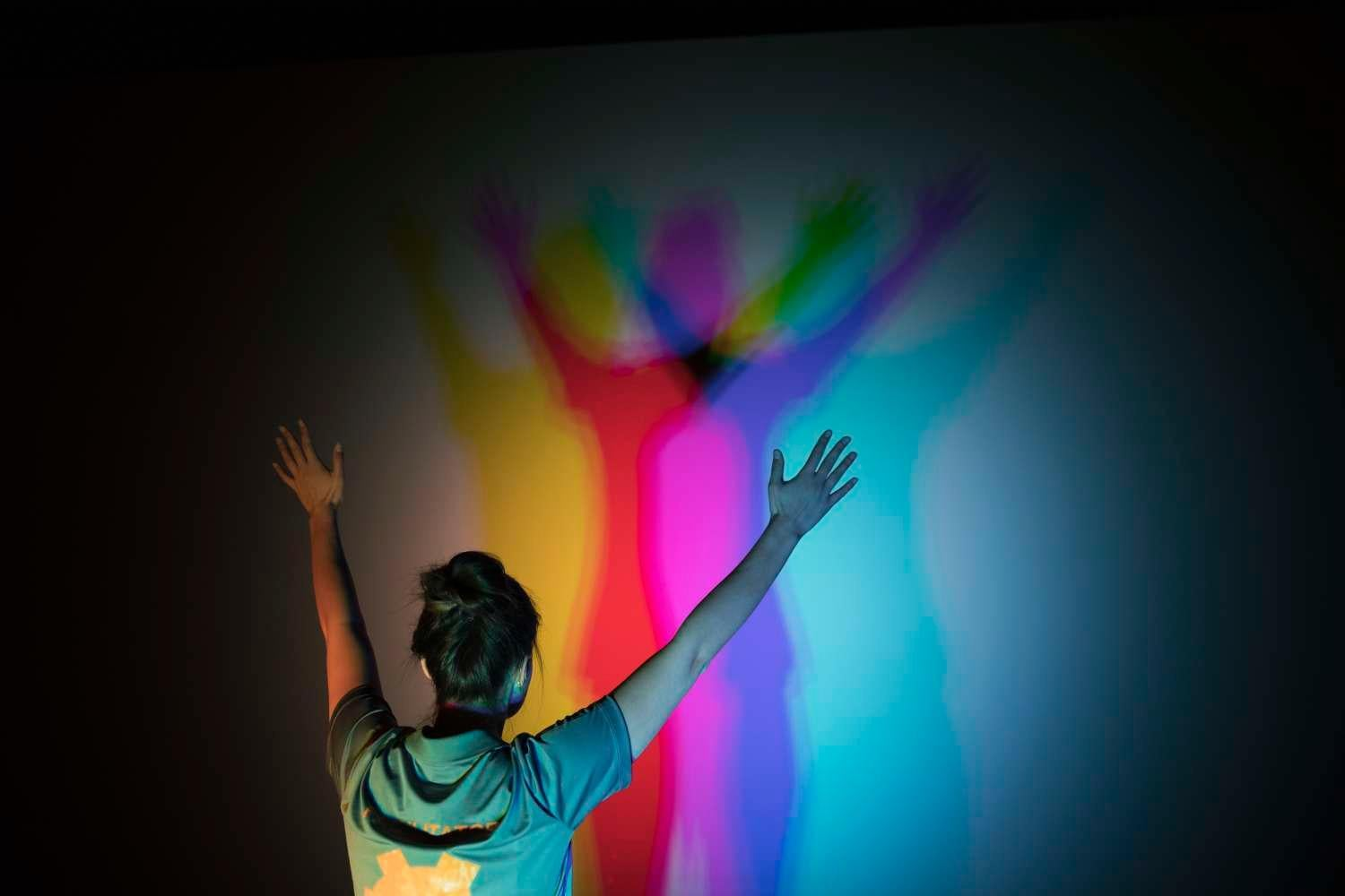 Woman with arms raised views her shadow as a spectrum of colors on wall