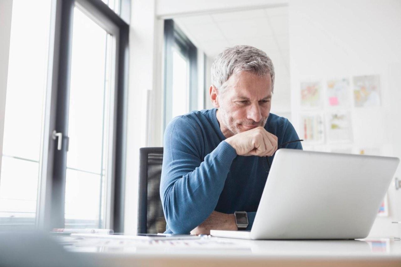 Mature man sitting in office using laptop