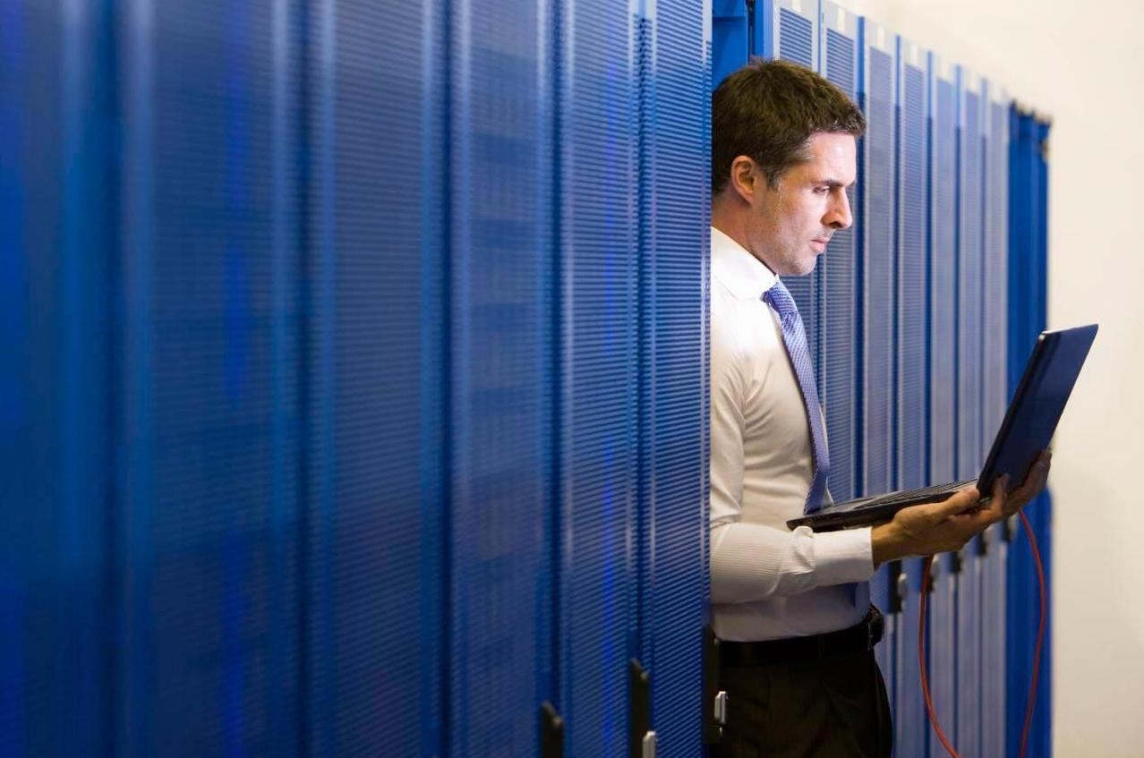 IT technician with laptop in network server room