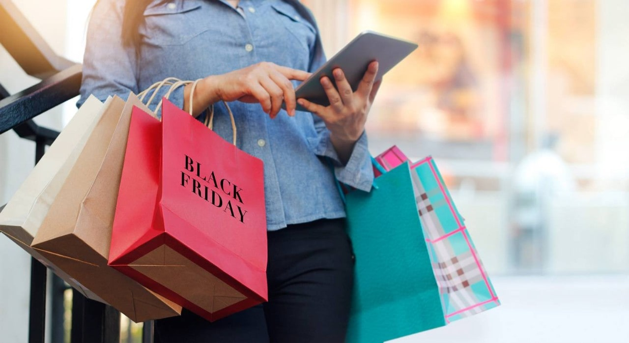 Woman Using Tablet while Holding Shopping Bags