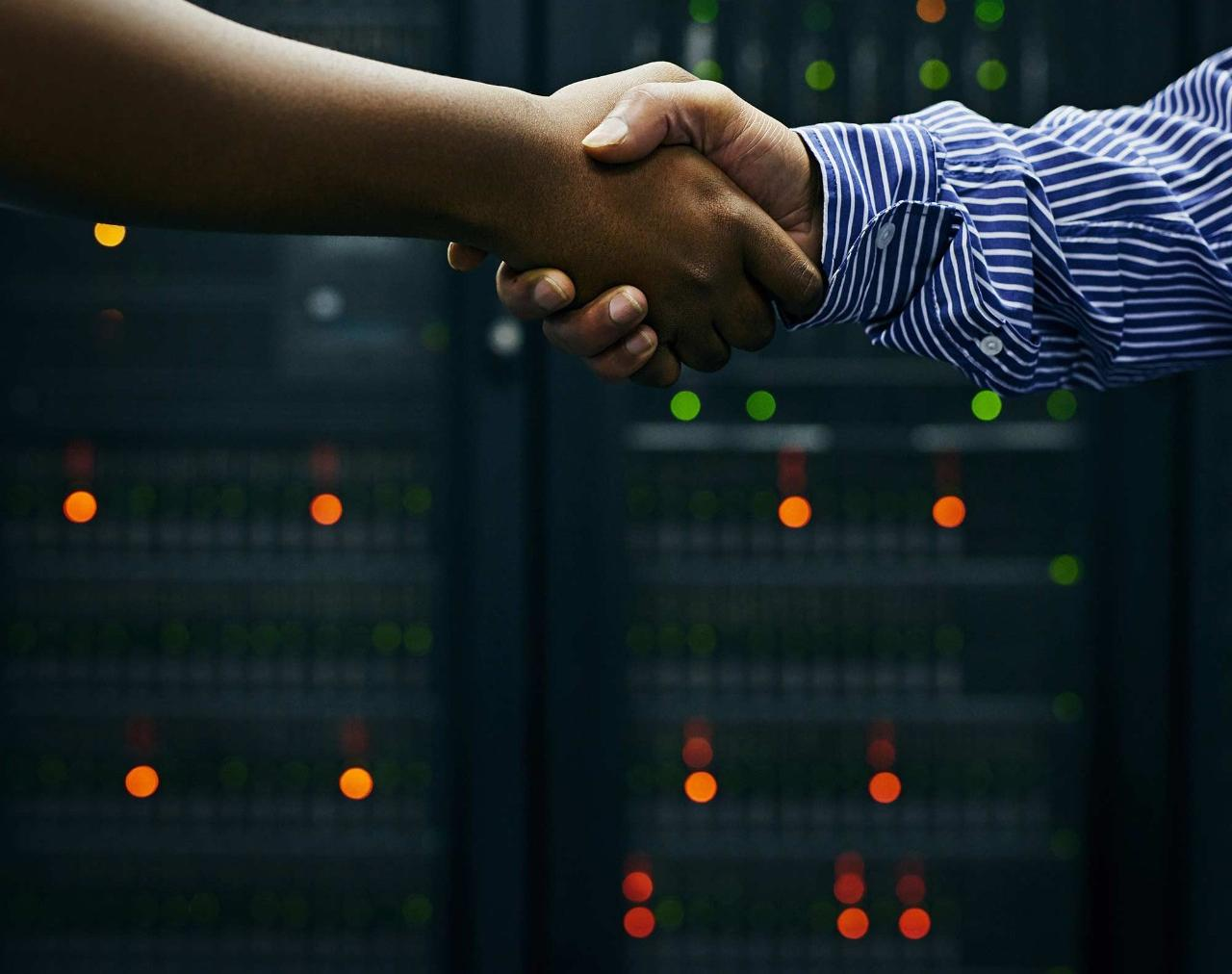 Cropped shot of two men shaking hands in a data center