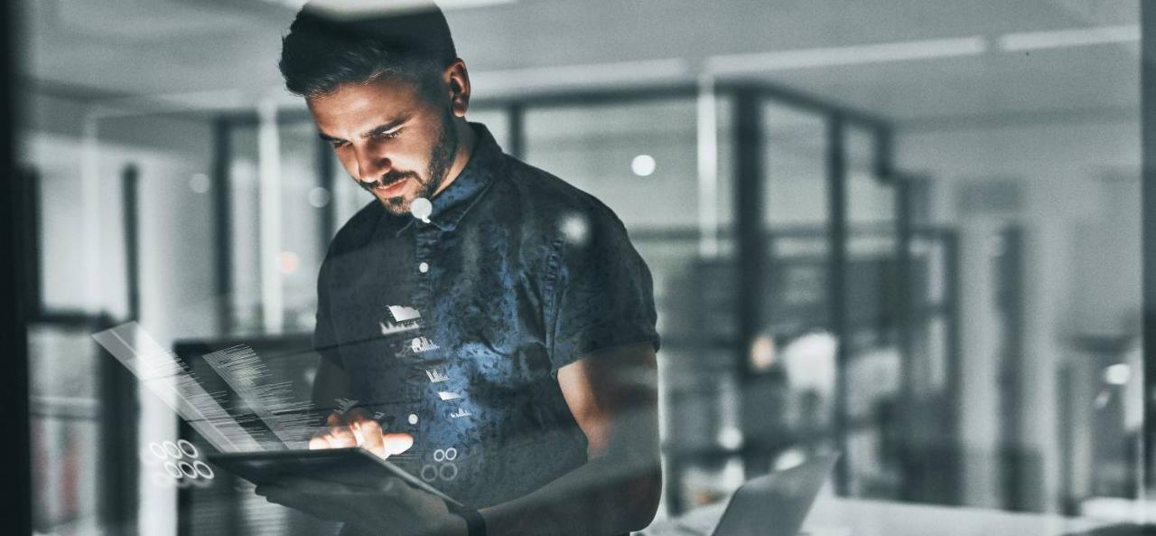 Man analyzing data on tablet in office