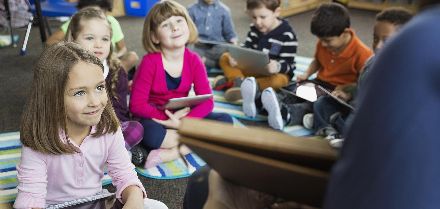 Teacher reading to class with students following along using tablets
