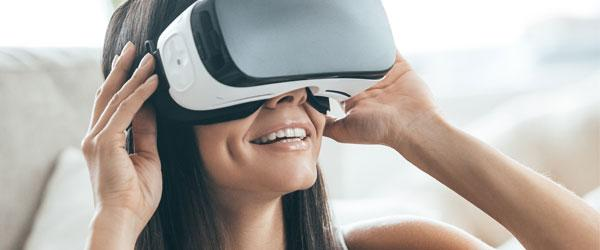 Future is now -- attractive young woman adjusting her VR headset and smiling while sitting at home