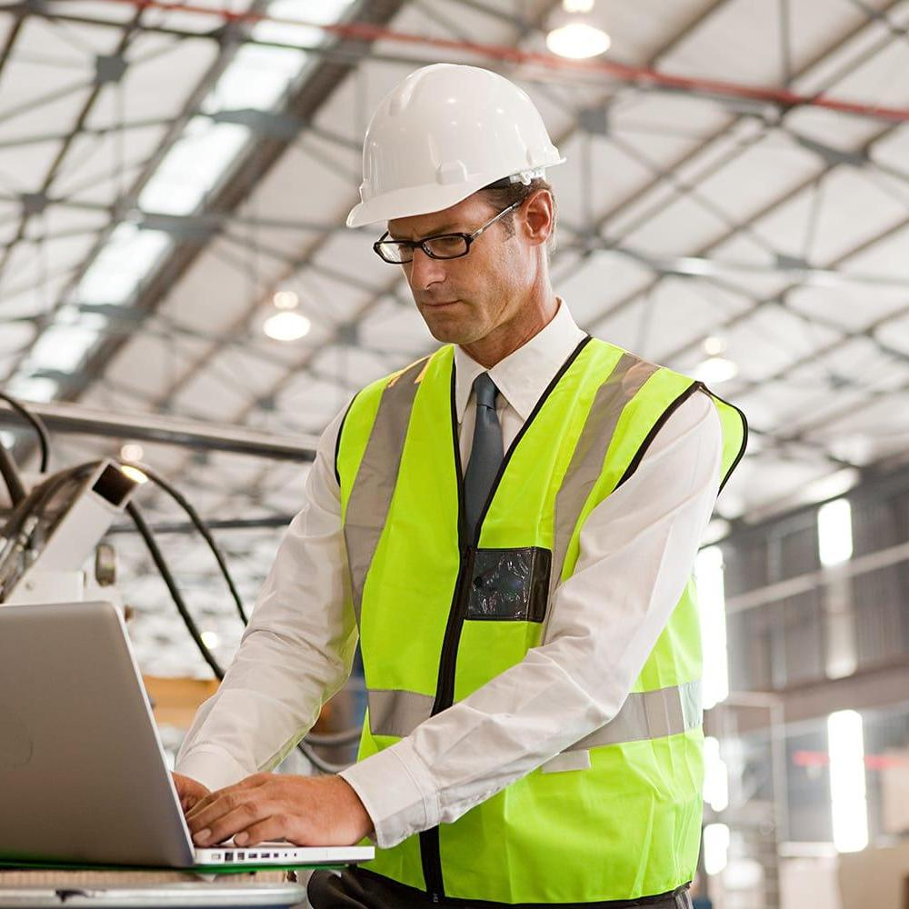 Head of manufacturing operations working on laptop on shop floor