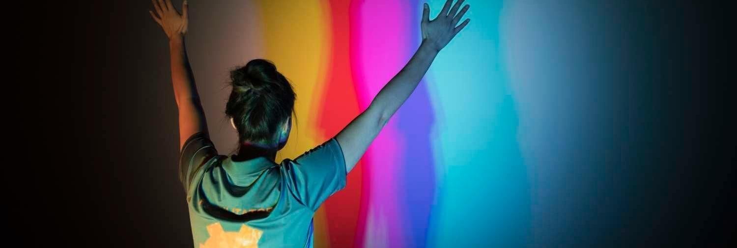 Young woman reaching arms into air in front of a colorful wall