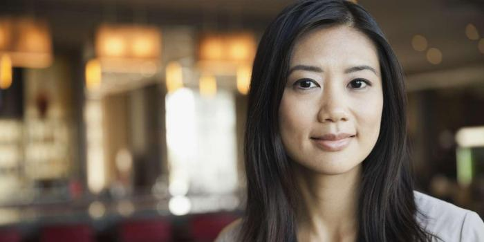 Asian woman with restaurant scene in background