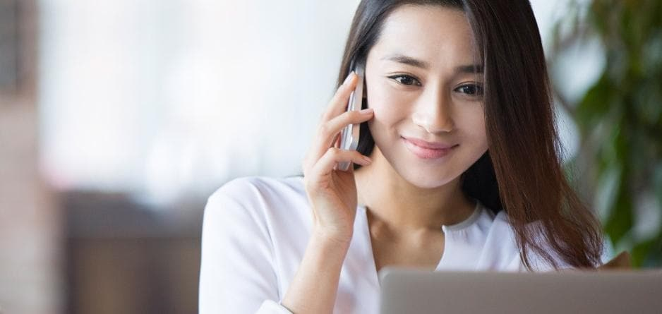 Young business woman at desktop computer and on mobile phone