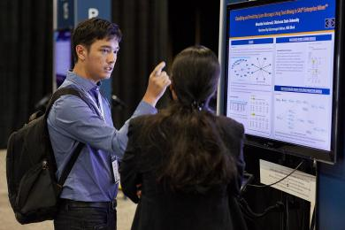 Man and woman discussing e-poster presentation at SAS Global Forum