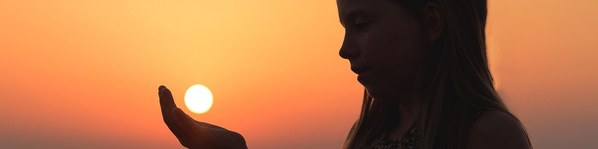 Young Girl Holding Sun At Sunset