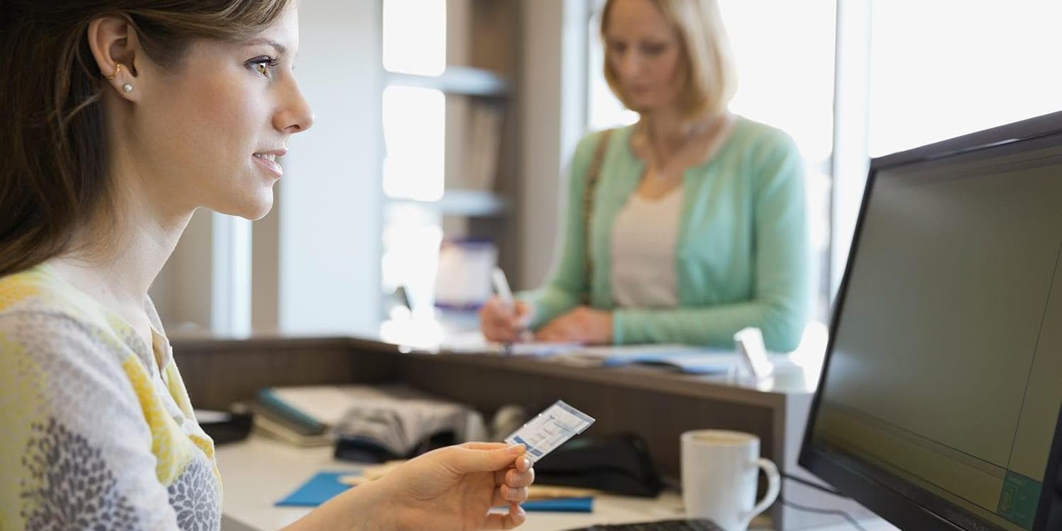 Woman paying at medical clinic front desk