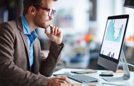 Man at Computer Looking at Charts