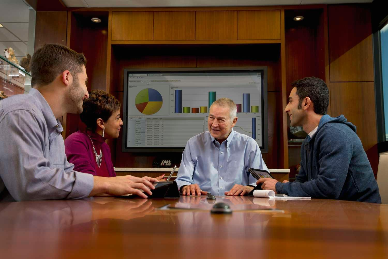 Jim Goodnight at a conference table talking to employees