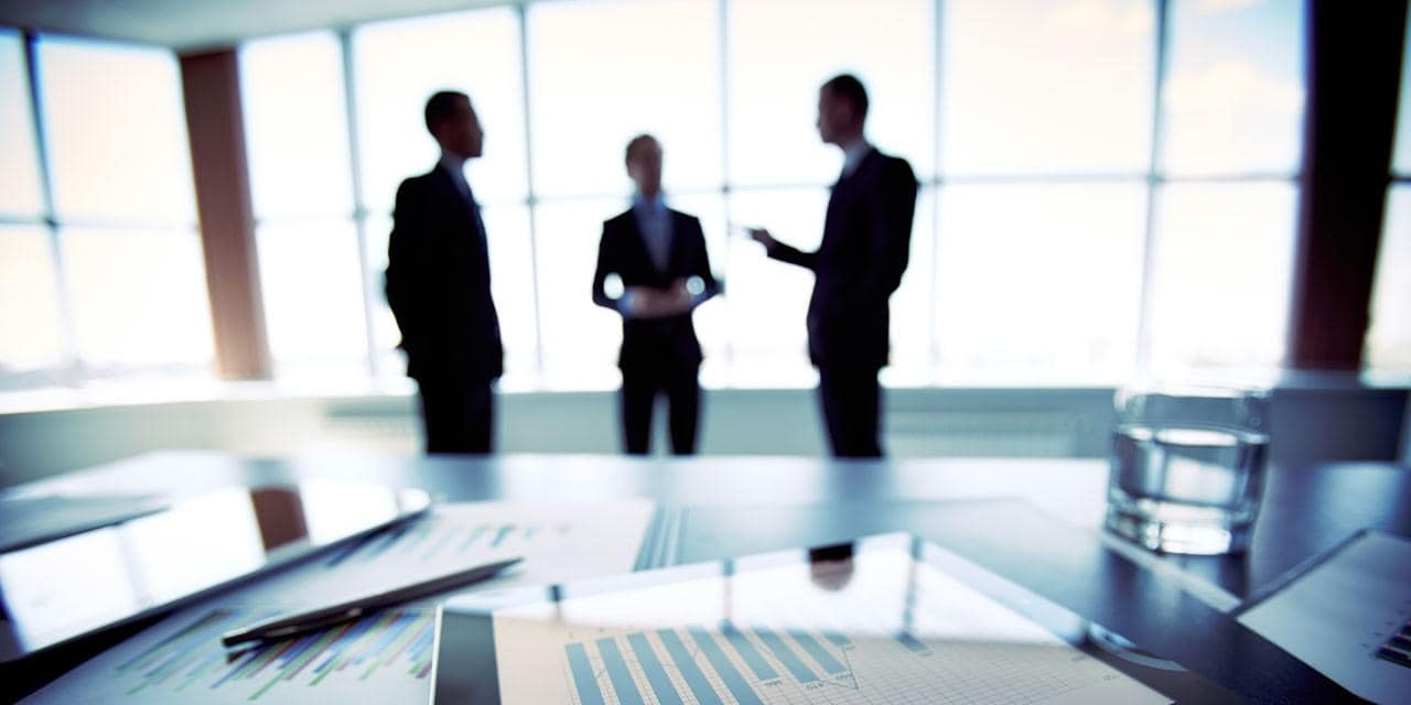 three business people discussing charts, reports