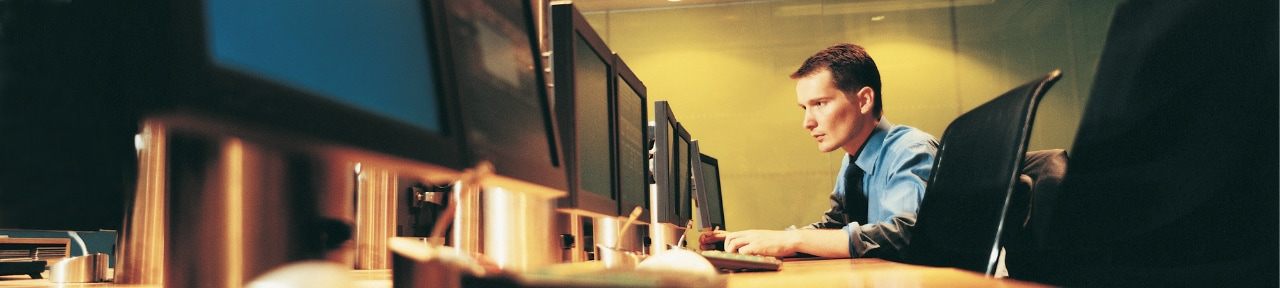 Professional male working on a computer in a capital markets setting