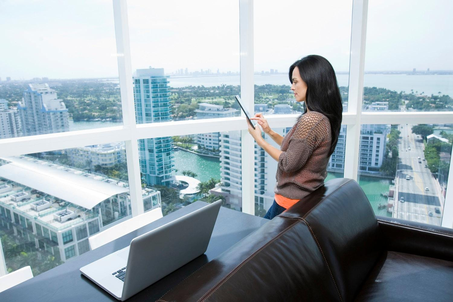 Businesswoman using digital tablet in office overlooking cityscape