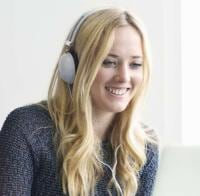 Young woman wearing headphones using laptop
